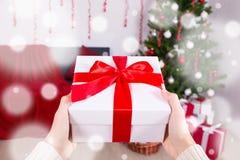 Άτομο που βάζει το κιβώτιο χριστουγεννιάτικου δώρου κάτω από το χριστουγεννιάτικο δέντρο στοκ φωτογραφίες