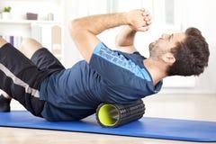Άτομο που βρίσκεται σε έναν κύλινδρο αφρού κάνοντας μια άσκηση