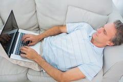 Άτομο που βρίσκεται στη δακτυλογράφηση καναπέδων στο lap-top Στοκ εικόνα με δικαίωμα ελεύθερης χρήσης