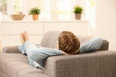 Άτομο που βρίσκεται στον καναπέ Στοκ Φωτογραφία