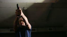 Άτομο που βλασταίνει ένα πυροβόλο όπλο βλαστοί ατόμων σε μια σειρά πυροβολισμού φιλμ μικρού μήκους