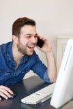 Άτομο που γελά και που εξετάζει τη οθόνη υπολογιστή Στοκ Φωτογραφία