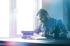 Άτομο που γράφει με τη μάνδρα και που διαβάζει τα βιβλία Στοκ φωτογραφία με δικαίωμα ελεύθερης χρήσης