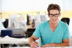 Άτομο που γράφει στο γραφείο στο απασχολημένο δημιουργικό γραφείο Στοκ Εικόνες