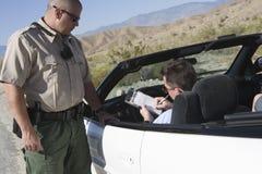 Άτομο που γράφει στο εισιτήριο με τον ανώτερο υπάλληλο κυκλοφορίας που υπερασπίζεται το αυτοκίνητο Στοκ Εικόνες