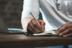 Άτομο που γράφει στο σημειωματάριο κατά τη διάρκεια της εργασίας καθμένος στον πίνακα με το lap-top Στοκ φωτογραφία με δικαίωμα ελεύθερης χρήσης
