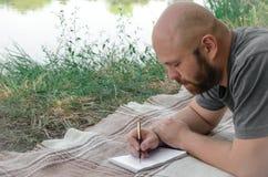 Άτομο που γράφει στο σημειωματάριό του στο δάσος στοκ εικόνες