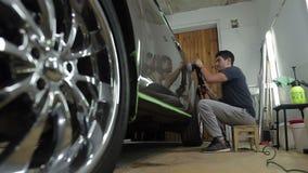 Άτομο που γυαλίζει το αυτοκίνητό του στο γκαράζ απόθεμα βίντεο