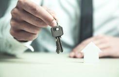 Άτομο που δίνει τα κλειδιά σπιτιών κτήμα έννοιας πραγματικό Στοκ εικόνα με δικαίωμα ελεύθερης χρήσης