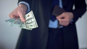 Άτομο που δίνει τη δέσμη των δολαρίων, αγορά στο κατάστημα, πληρωμή της ποινικής ρήτρας, ανταπόδοση στοκ φωτογραφία