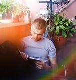 Άτομο που διαβάζει ένα βιβλίο σε ένα σπίτι στοκ φωτογραφίες