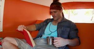 Άτομο που διαβάζει το μυθιστόρημα ενώ έχοντας τον καφέ camper van 4k απόθεμα βίντεο