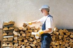 Άτομο που διατάζει το καυσόξυλο από τον τοίχο σπιτιών Στοκ φωτογραφία με δικαίωμα ελεύθερης χρήσης