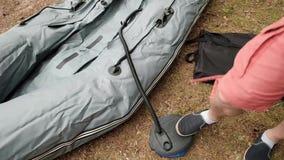 Άτομο που διογκώνει τη λαστιχένια βάρκα για την αλιεία από το πόδι του στην ακτή απόθεμα βίντεο