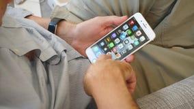 Άτομο που δοκιμάζει το πιό πρόσφατο iPhone 8 συν app φιλμ μικρού μήκους