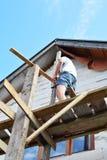 Άτομο που εγκαθιστά τα ξύλινα υλικά σκαλωσιάς στοκ φωτογραφία με δικαίωμα ελεύθερης χρήσης