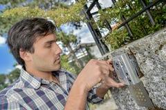 Άτομο που εγκαθιστά την ηλεκτρονική συσκευή ασφάλειας στον εξωτερικό τοίχο στοκ εικόνα με δικαίωμα ελεύθερης χρήσης