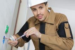 Άτομο που εγκαθιστά την ηλεκτρική έξοδο στο λουτρό στοκ φωτογραφία