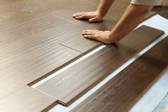 Άτομο που εγκαθιστά το νέο φυλλόμορφο ξύλινο δάπεδο στοκ φωτογραφία