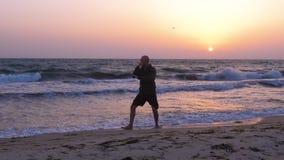 Άτομο που εκπαιδεύει Tai Chi τη chuan πειθαρχία υπαίθρια στην παραλία θάλασσας βραδιού ενώ ηλιοβασίλεμα απόθεμα βίντεο