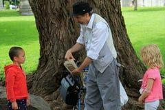 Άτομο που εκτελεί τα τεχνάσματα καρτών με το νέα αγόρι και το κορίτσι στο πάρκο, Saratoga Springs, Νέα Υόρκη, 2014 Στοκ Εικόνες