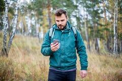 Άτομο που ελέγχει το χάρτη στο τηλέφωνο πεζοποριες σε ένα δάσος στοκ εικόνες με δικαίωμα ελεύθερης χρήσης