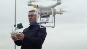 Άτομο που ενεργοποιεί ένα τετράγωνο κηφήνων copter με την εν πλω ψηφιακή κάμερα απόθεμα βίντεο