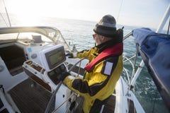 Άτομο που ενεργοποιεί την πλοήγησης οθόνη στη βάρκα πανιών στη θάλασσα στοκ φωτογραφία με δικαίωμα ελεύθερης χρήσης