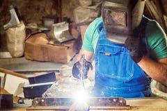 Άτομο που ενώνει στενά ένα μέταλλο με τη μηχανή συγκόλλησης τόξων στοκ φωτογραφίες