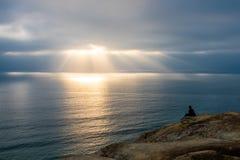 Άτομο που εξετάζει έξω τις ακτίνες του φωτός πέρα από τον ωκεανό στοκ εικόνες