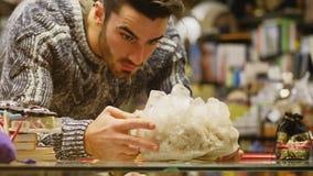 Άτομο που εξετάζει τα αγαθά στο κατάστημα, μεγάλο κρύσταλλο χαλαζία Στοκ Φωτογραφία