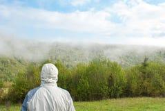 Άτομο που εξετάζει την ομίχλη πρωί λιβαδιών ομίχλης πέρα από το ύδωρ Δάσος στην ομίχλη Στοκ Εικόνες