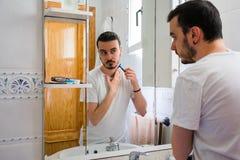 Άτομο που εξετάζει τον σε έναν καθρέφτη στο λουτρό Ξυρίζει τη γενειάδα του στοκ φωτογραφία με δικαίωμα ελεύθερης χρήσης