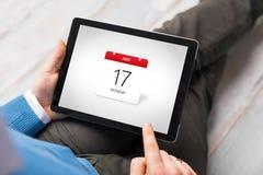 Άτομο που εξετάζει το ημερολόγιο app στον υπολογιστή ταμπλετών Στοκ Εικόνες