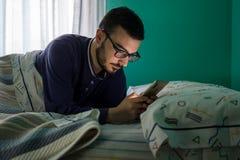Άτομο που εξετάζει το κινητό τηλέφωνό του στο κρεβάτι το πρωί στοκ εικόνα