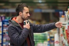Άτομο που εξετάζει το κινητό τηλέφωνο στο εμπορικό κέντρο Στοκ Φωτογραφία