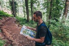 Άτομο που εξετάζει το χάρτη πεζοποριες στο δάσος στοκ εικόνες