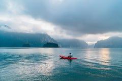 Άτομο που επιπλέει στο καγιάκ στη λίμνη του τοπικού LAN Cheow στο εθνικό πάρκο Khao Sok, Ταϊλάνδη στο χρόνο ξημερωμάτων στοκ εικόνα με δικαίωμα ελεύθερης χρήσης