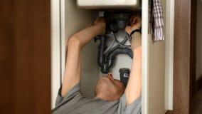 Άτομο που επισκευάζει έναν νεροχύτη κουζινών απόθεμα βίντεο