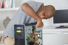 Άτομο που επισκευάζει τον υπολογιστή καθμένος στη θέση εργασίας Στοκ Εικόνες