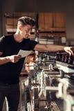 Άτομο που εποπτεύει τη διαδικασία της εμφιάλωσης μπύρας στο ζυθοποιείο Στοκ Φωτογραφίες