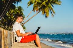 Άτομο που εργάζεται με ένα lap-top, στην παραλία Στοκ Εικόνες