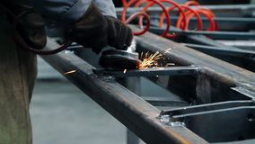 Άτομο που εργάζεται με την ηλεκτρική λείανση ροδών στη δομή χάλυβα στο εργοστάσιο φιλμ μικρού μήκους