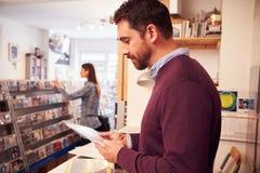 Άτομο που εργάζεται πίσω από το μετρητή σε ένα κατάστημα αρχείων Στοκ Εικόνες