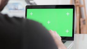Άτομο που εργάζεται σε ένα lap-top με μια πράσινη επίδειξη οθόνης φιλμ μικρού μήκους
