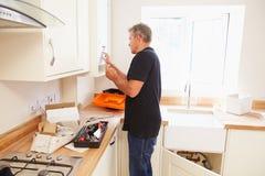 Άτομο που εργάζεται σε μια νέα εγκατάσταση κουζινών Στοκ Φωτογραφίες