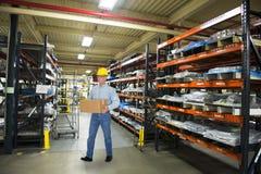 Άτομο που εργάζεται στη βιομηχανική αποθήκη εμπορευμάτων κατασκευής Στοκ Φωτογραφίες