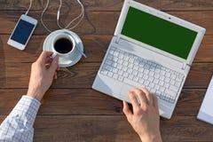 Άτομο που εργάζεται στον υπολογιστή στην ξύλινη υπερυψωμένη άποψη γραφείων Στοκ Φωτογραφίες