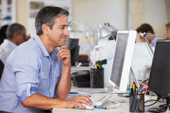 Άτομο που εργάζεται στο γραφείο στο απασχολημένο δημιουργικό γραφείο