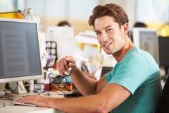 Άτομο που εργάζεται στο γραφείο στο πολυάσχολο δημιουργικό γραφείο Στοκ Φωτογραφίες